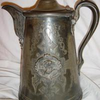 Pewter Pitcher with a lady riding a bat.